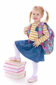 Cheerful schoolgirl with satchel behind him holding his leg on a — Stock Photo