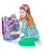 Charming schoolgirl on her knees opens his satchel — Stock Photo
