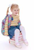 Charming little schoolgirl with satchel behind him sitting on a — Stock Photo