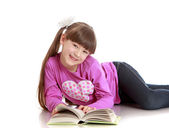 Charming schoolgirl reading a book lying on the floor — Stock Photo