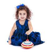 Little girl spinning dreidel sitting on the floor — Stock Photo