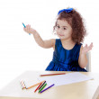 Very smart little girl draws with pencils sitting at the table — Stock Photo #75667313