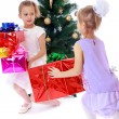 Girls sisters around the Christmas tree fuss considering boxes w — Stock Photo #75665781