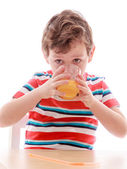 The little boy eagerly drinking juice from a glass , close-up — Stock Photo