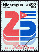 NICARAGUA - CIRCA 1984: A stamp printed in Nicaragua issued for the 25th anniversary of Cuban Revolution shows number 25 and the Cuban Flag, circa 1984. — Stockfoto