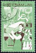 """Vietnã - Circa 1987: Um selo imprimido no Vietnã desde o """"6ª festa Congresso decisões"""" questão mostra o aumento da produção Industrial (mulher carregando fardos de pano), por volta de 1987. — Fotografia Stock"""