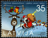 "LATVIA - CIRCA 2011: A stamp printed in Latvia from the ""Christmas "" issue shows Deer and Santa Claus, circa 2011. — Foto de Stock"