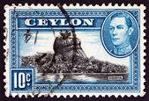 CEYLON - CIRCA 1938: A stamp printed in Ceylon shows Sigiriya (Lion Rock) and King George VI, circa 1938. — Stock Photo