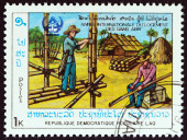 """LAOS - CIRCA 1987: A stamp printed in Laos from the """"International Year of Shelter for the Homeless """" issue shows building bamboo house, circa 1987. — Stock Photo"""