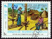Laos - Circa 1987 : Un timbre imprimé au Laos de l'affiche de question « Année internationale du logement des sans-abri » construction de maison en bambou, vers 1987. — Photo