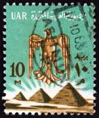 EGYPT - CIRCA 1964: A stamp printed in Egypt shows Eagle emblem and the Three Pyramids at Giza, circa 1964. — Stock Photo