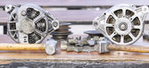 Carburetors hammers and gears on a wooden table — Stock Photo