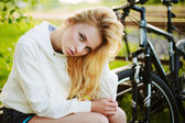 Beautiful girl sitting against bike outdoor in the park — Stock Photo