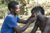 Hamar men paint each other's face in a preparation to a bull jum — Stock Photo