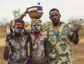 Boys from Mursi tribe and a solder with machine guns in Mirobey. Omo Valley. Ethiopia. — Stock Photo