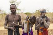Boys and a man from Mursi tribe with spears in Mirobey village. Omo Valley. Ethiopia. — Stock Photo