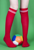 Red socks long legs and football — Stock Photo