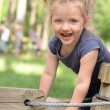 Very happy little girl playing in high wire park — Stock Photo #54669461