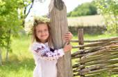Smiling hirl standing near wooden fence — Zdjęcie stockowe