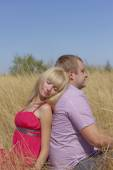 Young couple in love in the open field are sitting back to back — Foto de Stock