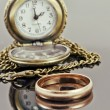 Pocket watch and a gold wedding ring on a reflective surface — Stock Photo #57235299