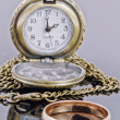 Pocket watch and a gold wedding ring on a reflective surface — Stock Photo #57235301