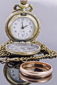 Pocket watch and a gold wedding ring on a reflective surface — Stock Photo