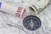 One-dollar, ten Euro bilsl and a compass lying on a map — Stock Photo