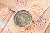 On the page of passports with visas lies with the compass — Stock Photo