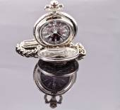 Silver pocket watch on a reflective surface — Stock Photo