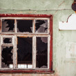 Smashed glass Window with old wooden frame on grunge wall damaged house — Stock Photo #53405107