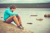 Young Man hipster relaxing alone outdoor with mountains and lake on background Lifestyle concept — Stock Photo