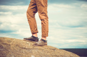 Feet man standing on rocky mountain outdoor Travel Lifestyle vacations concept with sky clouds on background retro colors — Stock Photo