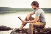 Young Man reading book outdoor with lake on background Summer vacations and Lifestyle concept — Stockfoto