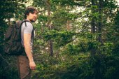 Young Man walking in forest with backpack Hiking Lifestyle and outdoor recreation concept — Stock Photo