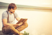Young Man reading book outdoor with lake on background Summer vacations and Lifestyle concept — ストック写真
