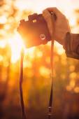 Man hand holding retro photo camera outdoor hipster Lifestyle with sun lights bokeh — Stock Photo