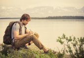 Young Man Traveler with backpack reading book and writing notes outdoor — Stock Photo