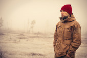 Young Man wearing winter hat clothing outdoor with foggy nature on background — Stock Photo
