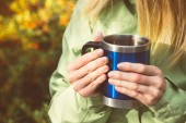 Metal touristic tea cup in Woman hands Outdoor Lifestyle and Hiking concept — Stock Photo