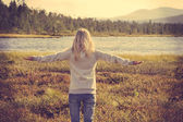 Young Woman relaxing outdoor hand raised Lifestyle vacations concept forest and lake on background trendy retro colors — Stok fotoğraf