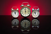Group of alarm clocks, red background — Stock Photo