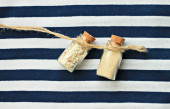 Little corked bottles with sand on stripy background — Stock Photo