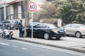 Dalian police officer writing parking ticket. — Stock Photo