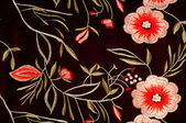Silk fabric texture dark brown with bright floral pattern — Stock Photo