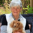 Senior lady in the garden with dog — Stock Photo #74796435