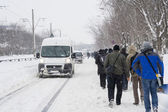 BUCHAREST - FEBRUARY 13 : Heavy snowfall of nearly 60 cm (2 feet) on February 13, 2012 has paralyzed the traffic. People left their cars and are walking on the road. — Stock Photo