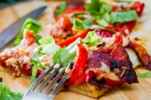 Slice of pizza with peppers, bacon and herbs on a wooden board — Foto de Stock