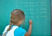 Girl writing lines on chalkboard — Stock Photo