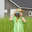 Girl in weeds with old camera — Stock Photo #56429367